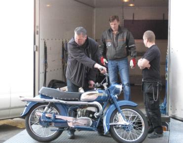Museomestarit Kim Karvinen ja Mikko Kärnä sekä autonkuljettaja Raimo Hakala tuovat Vapriikkiin Erkki Pietolan omistamaa Husqvarna Drömbågen, 175 ksm, -moottoripyörää vuodelta 1957.